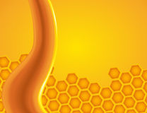 Honey dripping on the honeycomb. Stream of honey dripping and honeycomb in the background. Golden bee nectar flowing Royalty Free Stock Image