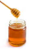 Honey dripping into jar over white. Honey dripping into jar isolated over white Royalty Free Stock Photos