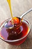 Honey dripping onto spoon Royalty Free Stock Photos