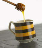 Honey dripping into pot Royalty Free Stock Photos