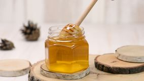 Honey dripping, pouring from honey dipper in a glass jar bowl. Healthy organic Thick honey dipping from the wooden honey spoon, closeup stock footage