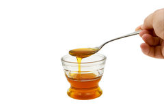 Honey dripping into small glass bowl Royalty Free Stock Images