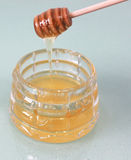 Honey dripping with special sticks in a jar for honey Stock Image