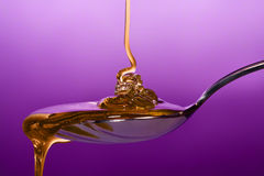 Honey dripping on spoon. Honey dripping on to a spoon and pouring over Stock Photo