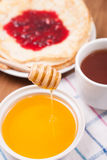 Honey dripping from a spoon pancakes and tea . Stock Photos