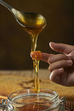 Honey dripping from a spoon Royalty Free Stock Photography