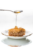 Honey dripping from sterling silver spoon onto baklava. Royalty Free Stock Photo