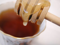 Honey dripping into tea. Honey stick dripping honey into hot cup of tea Stock Photo