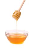 Honey dripping from a wooden dipper. Stock Photography
