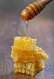 Honey dripping from a wooden drizzler Stock Photo