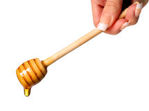 Honey dripping. Wooden honey dipper in female hand isolated Royalty Free Stock Photography