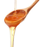 Honey dripping from a wooden honey dipper isolated on white back Royalty Free Stock Photography