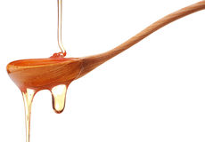 Honey dripping from a wooden honey dipper isolated on white back Royalty Free Stock Image