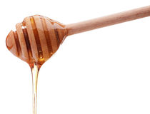 Honey dripping from a wooden honey dipper isolated on white back Stock Image