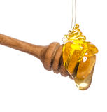 Honey dripping from a wooden honey dipper Stock Images