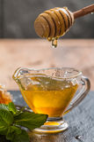 Honey dripping from a wooden honey dipper Royalty Free Stock Image