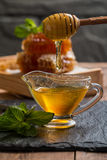 Honey dripping from a wooden honey dipper Stock Image