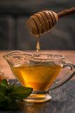 Honey dripping from a wooden honey dipper Stock Photos