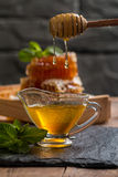 Honey dripping from a wooden honey dipper Royalty Free Stock Photo