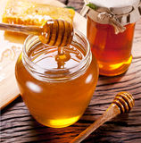 Honey dripping from wooden spoon. Stock Images