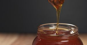 Honey drips from dipper in glass jar. Wide photo Stock Photography