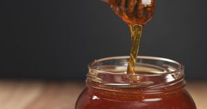 Honey drips from dipper in glass jar. Wide photo Stock Image