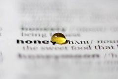 Honey drop. On a printed sheet Royalty Free Stock Photos