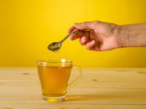 Honey falling from spoon in a glass of tea with lemon Stock Images