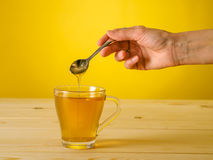Honey falling from spoon in a glass of tea with lemon Stock Photography