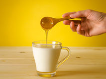 Honey falling from wooden spoon in a glass of milk Royalty Free Stock Photo