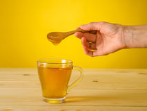 Honey falling from wooden spoon in a glass of tea with lemon Stock Image
