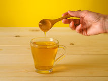 Honey falling from wooden spoon in a glass of tea with lemon Royalty Free Stock Photography