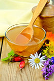 Honey with flowers and spoon on board Royalty Free Stock Image