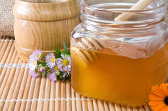 Honey and flowers on wood Stock Photography