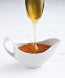 Honey flowing down. From a spoon Stock Image