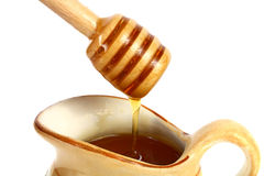 Honey flowing down from a wooden stick Royalty Free Stock Images