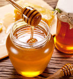Honey flowing into glass can from wooden stick. Stock Photo
