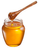 Honey flowing into glass jar. Stock Photo