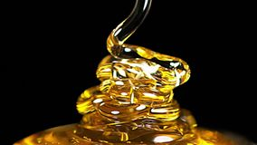 Honey Flowing tegen Zwarte Achtergrond, stock footage