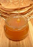 Honey flows from above in a glass jar against pancakes Stock Photo