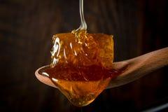 Honey Flows Over Comb na colher de madeira fotografia de stock royalty free