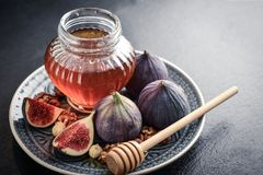 Honey with fresh figs. And nuts on slate black background closeup Stock Image
