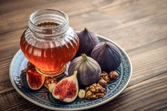 Honey with fresh figs. And nuts on wooden background closeup Royalty Free Stock Images