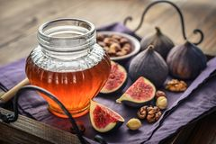 Honey with fresh figs and nuts. On tray on wooden background closeup Stock Images