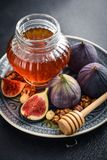 Honey with fresh figs. And nuts on slate black background closeup Royalty Free Stock Images
