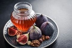 Honey with fresh figs and nuts. On slate black background closeup Stock Photo