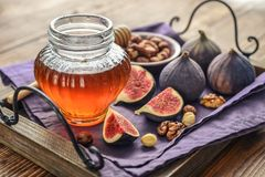 Honey with fresh figs. And nuts on tray on wooden background closeup Royalty Free Stock Images