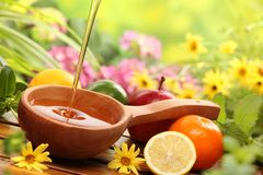 Honey and fresh fruits. With flowers background,closeup royalty free stock image