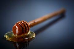 Honey. Fresh liquid honey with a honey spoon on a black background Royalty Free Stock Photography
