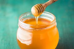 Honey in a glass bottle On blue wood in low light. In door stock photography